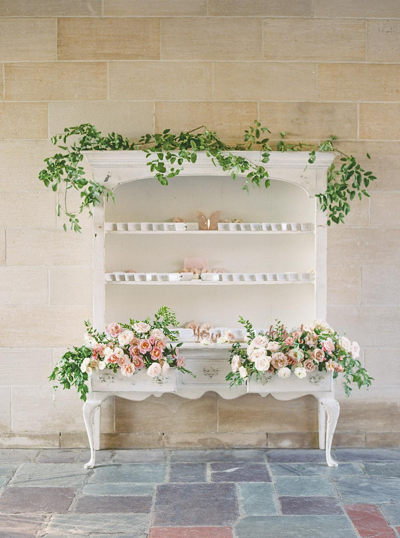 vintage hutch with flowers and greenery coming out of the drawers and escort cards displayed on shelf