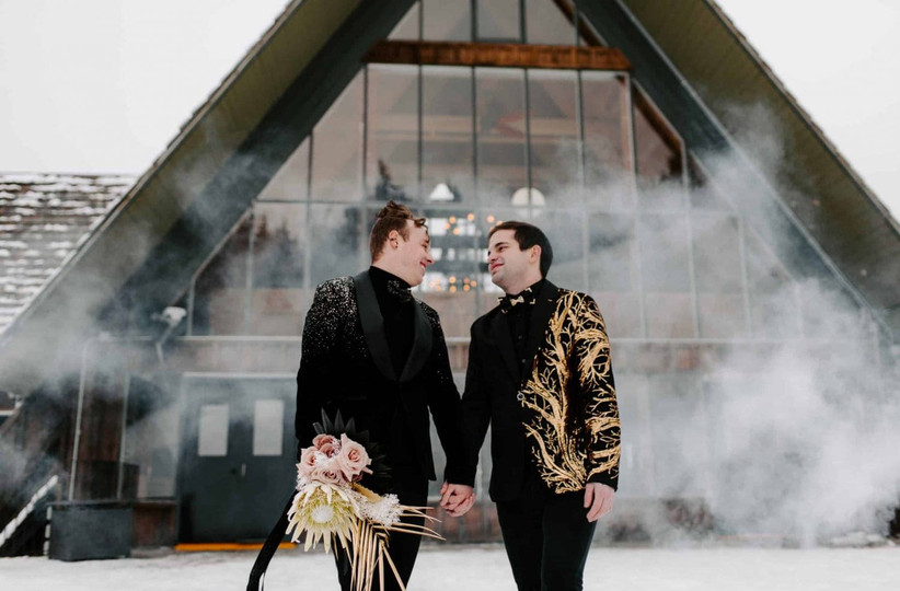 same-sex couple holds hands at outdoor winter wedding in the snow. they are both wearing all black with metallic gold and silver jackets