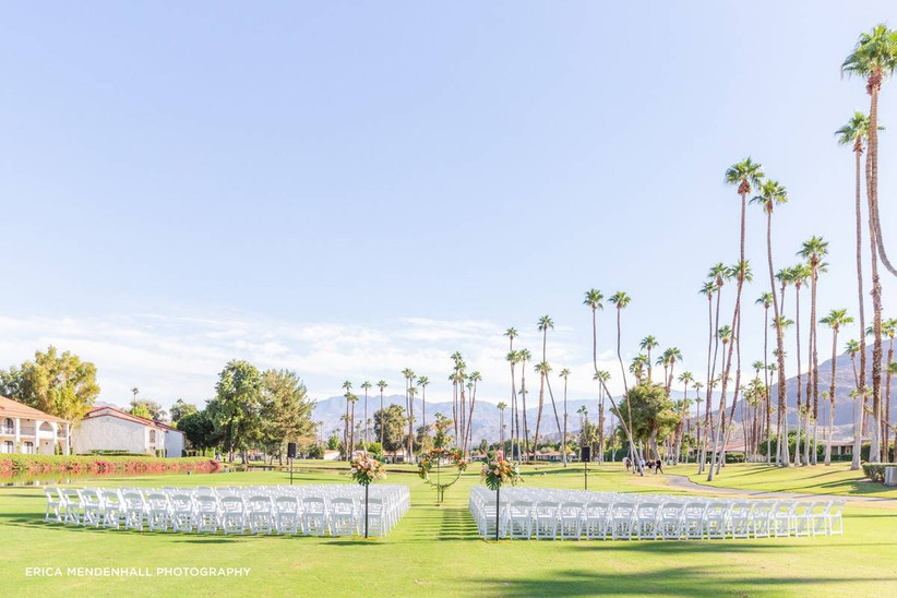 outdoor wedding ceremony with palm trees and mountain backdrop
