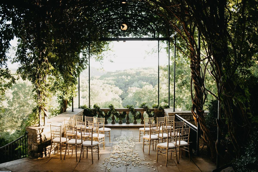 stone terrace under an archway of vines and greenery. rose petals are scattered on the floor and the terrace overlooks hills in the distance