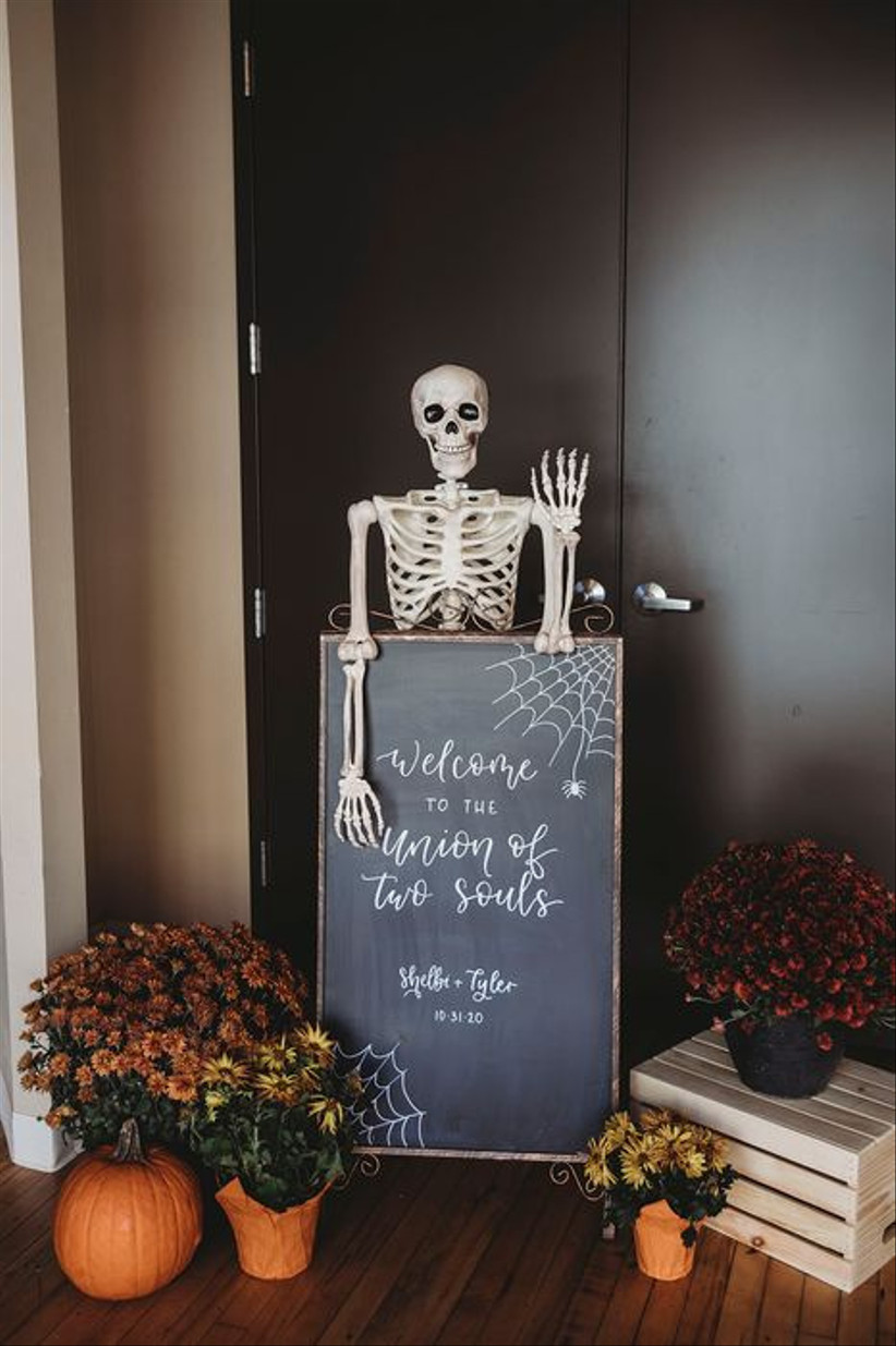 halloween themed wedding idea chalkboard welcome sign displayed with life-size skeleton