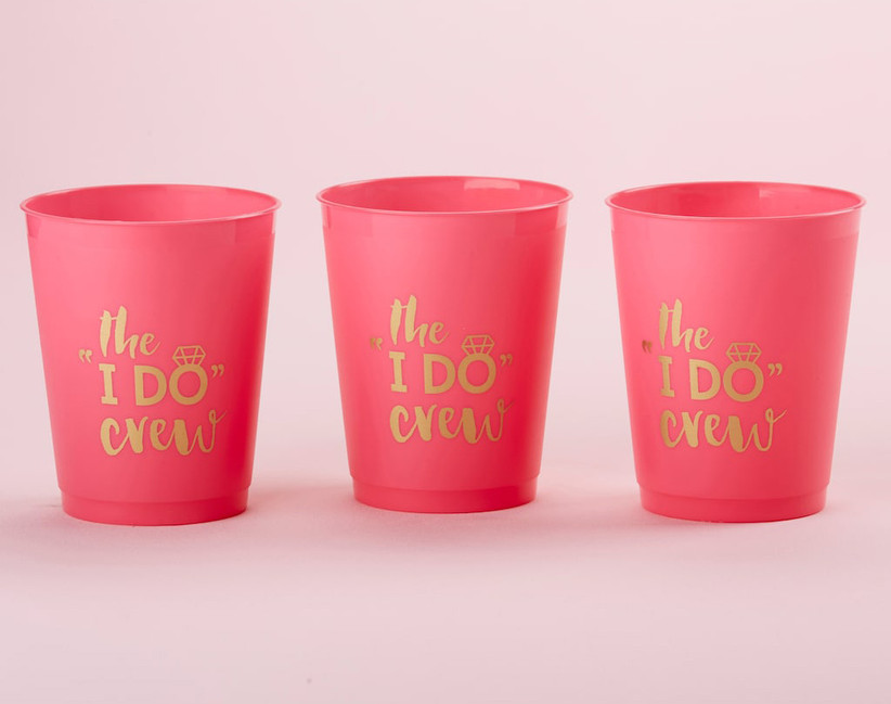 Three pink stadium cups in a row with The I Do Crew in gold lettering