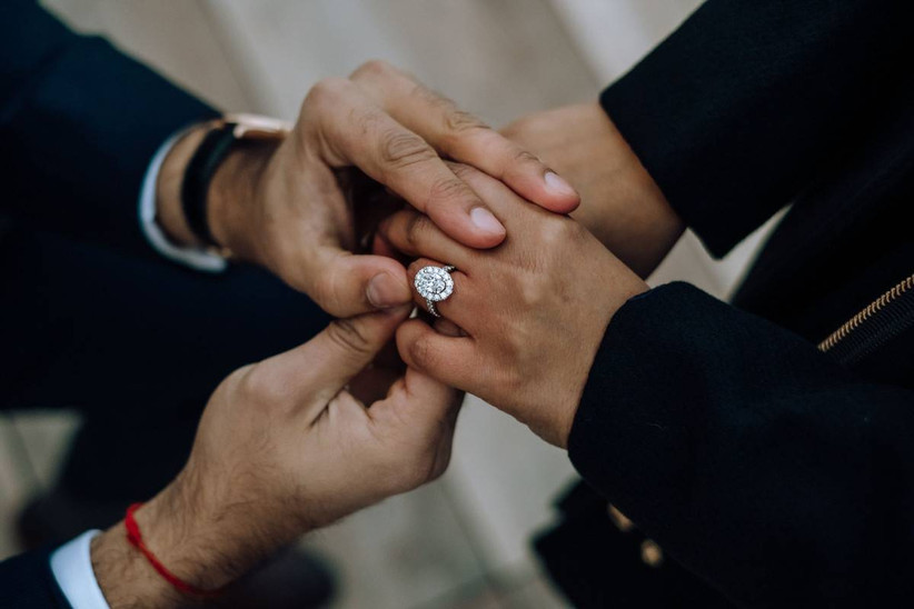 man placing engagement ring on woman's finger