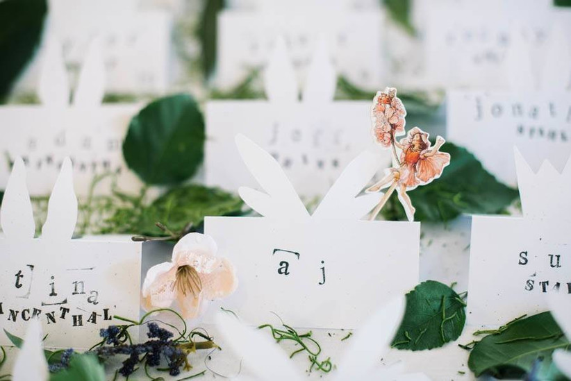 handmade wedding escort cards with names stamped in black ink and miniature paper fairy figurine on top