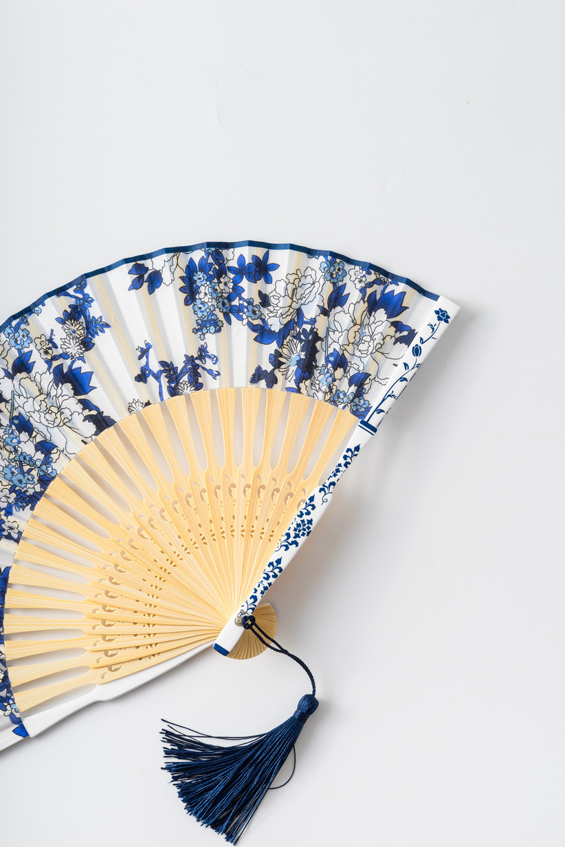 accordion fan decorated with white and blue floral print and a tassel on the bottom