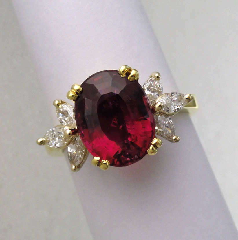 oval cut ruby engagement ring with yellow gold setting and side accent diamonds