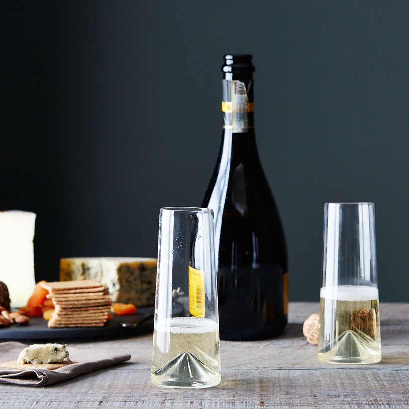 Table spread with cheese board, champagne bottle, and two stemless champagne flutes