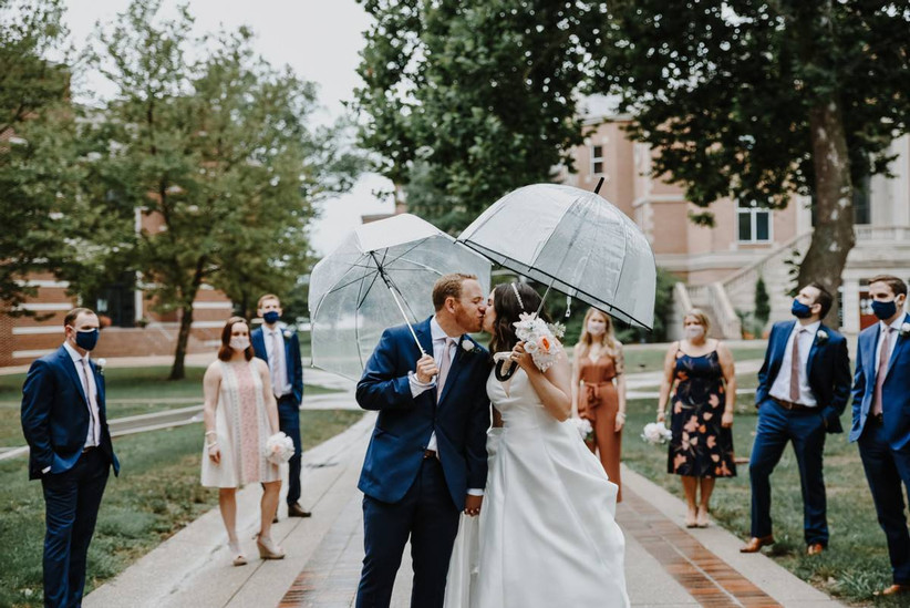 bride and groom kissing under umbrellas with guests wearing masks watching