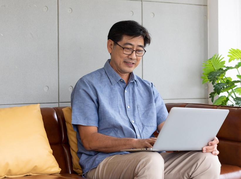 Older man sitting on sofa smiling using laptop