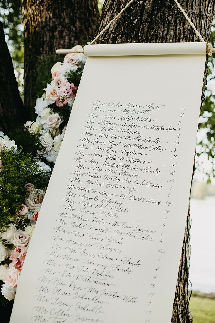 wedding seating chart in the shape of a life-sized scroll leaning against a tree decorated with garden roses