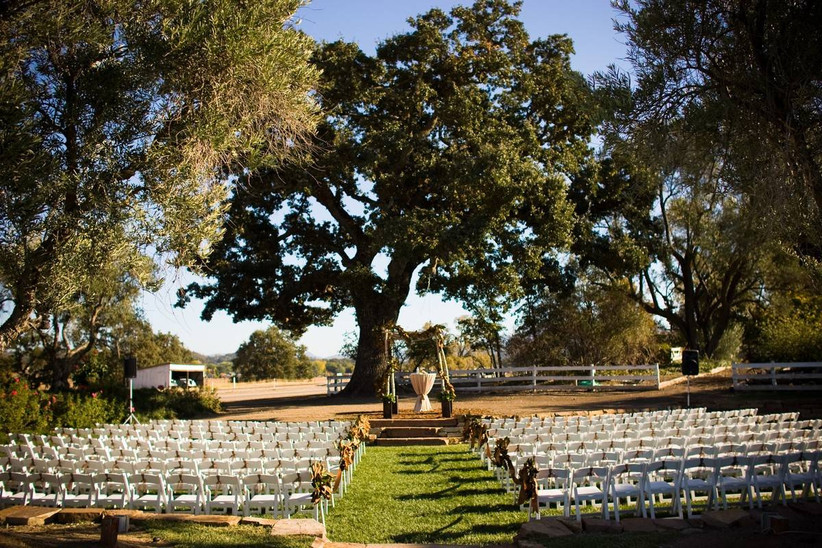 outdoor ceremony at Santa barbara wedding venue rows of white folding chairs are lined up on the grass facing large shady tree