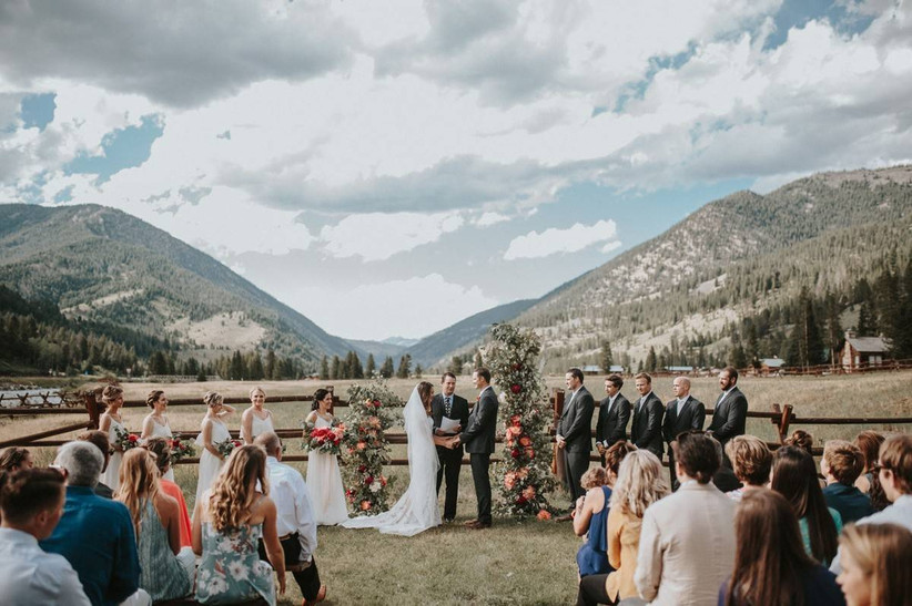 bride and groom hold hands at an outdoor wedding ceremony with mountain views