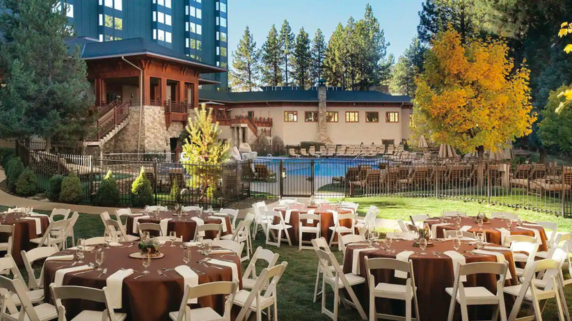 outdoor wedding reception with round tables and pool in the background