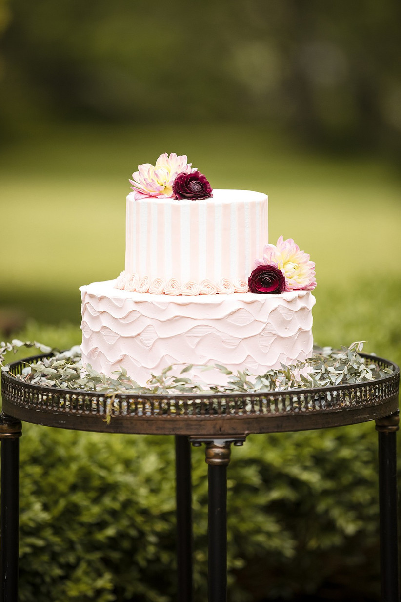 light pink wedding cake decorated with white stripes and dark red flowers