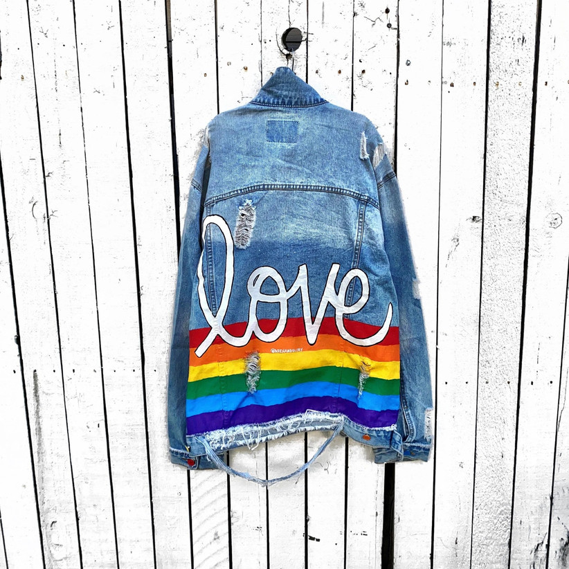 Blue frayed denim jacket with hand-painted rainbow stripes and Love calligraphy in white