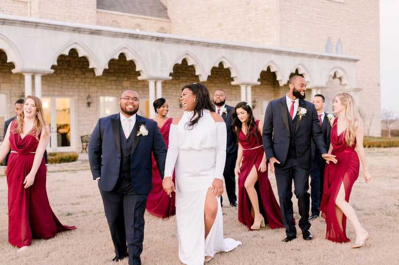 bride and groom laugh as they walk outdoors with their wedding party
