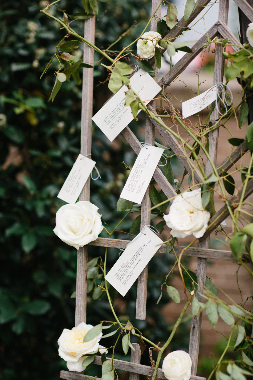 well-wishes cards tied to wooden lattice covered in vines and white roses