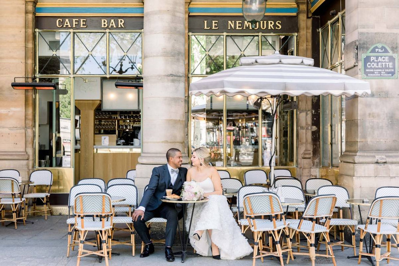 bride and groom in wedding attire sitting out front of french bistro in paris