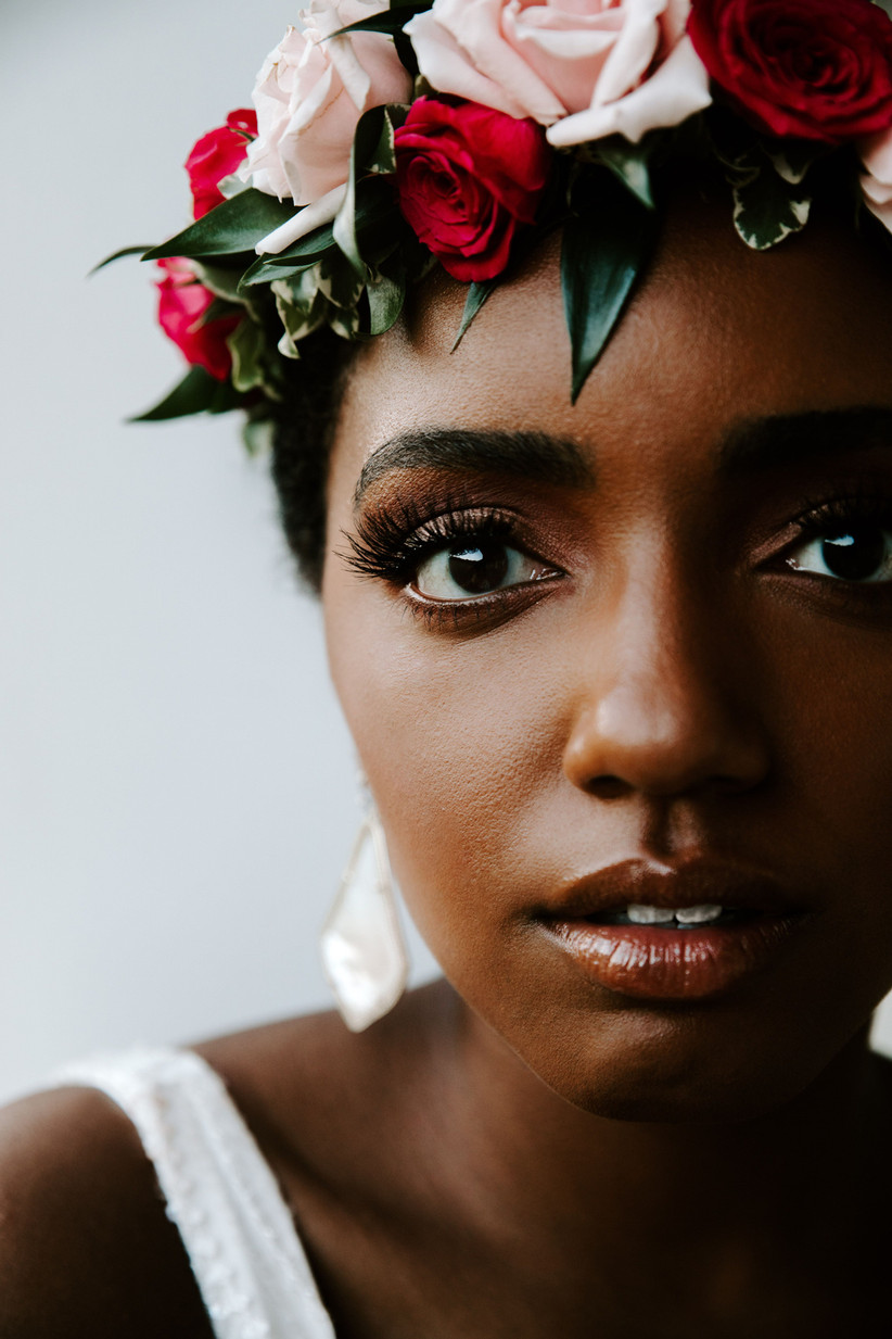 Black bride wearing flower crown of blush and red spray roses with greenery
