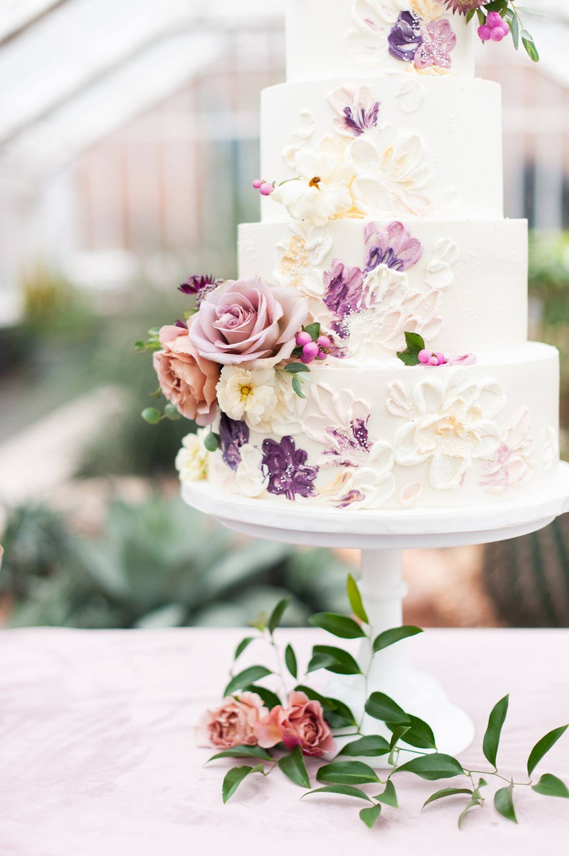 white four-tier wedding cake decorated with hand-painted buttercream flowers and fresh roses