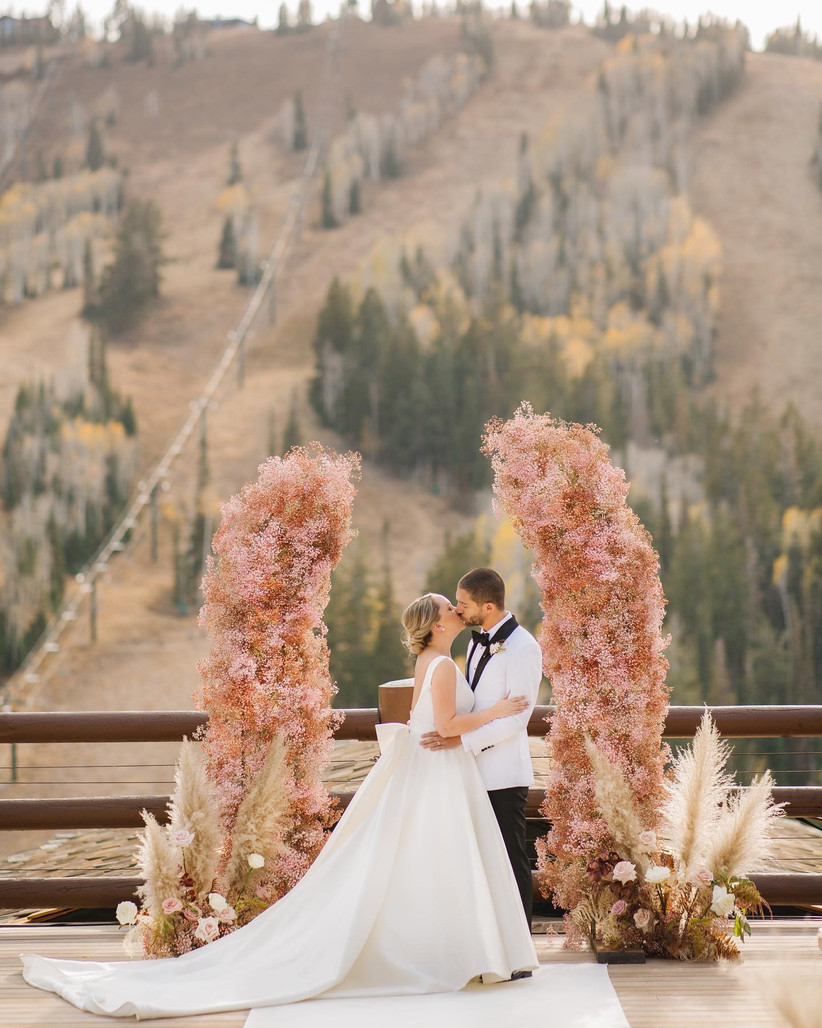 bride and groom kiss with mountain view in the background and pink floral arch surrounding them