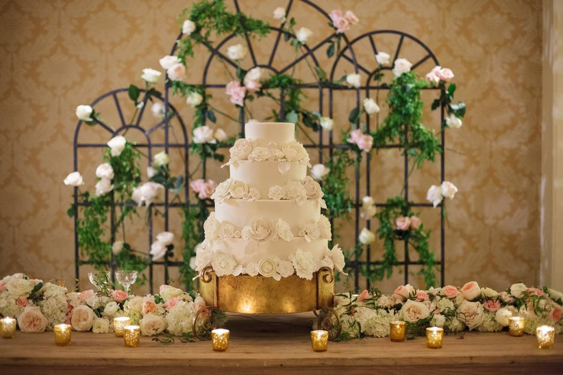 white four-tier fondant wedding cake decorated with white sugar flowers is displayed on a gold stand with roses and candles along the table