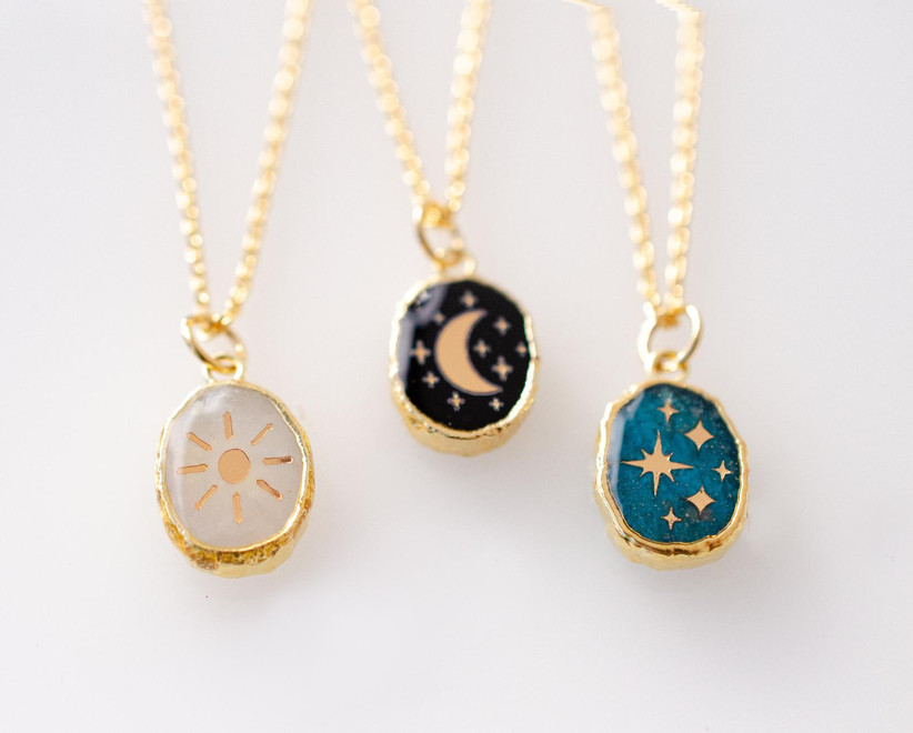 Three gorgeous pendants from left to right: the sun on moonstone, the moon on onyx, the stars on apatite