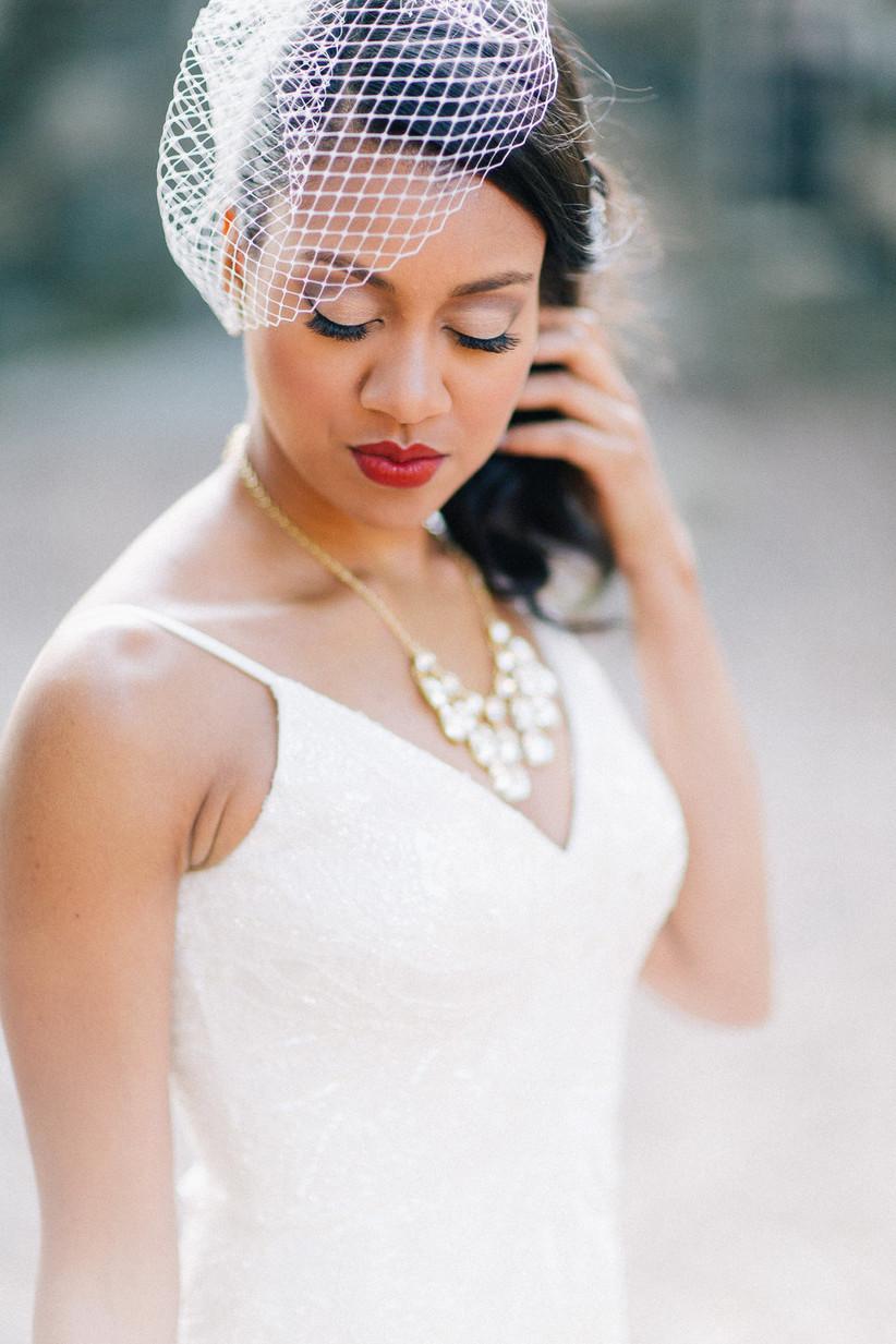 Black bride wears birdcage wedding veil with red lipstick