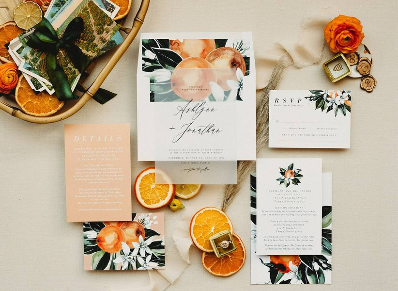 modern wedding flat lay with fresh citrus fruits and invitation suite