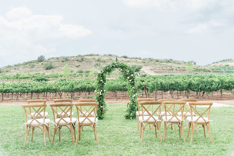 outdoor wedding ceremony with vineyard view and mountains in the background