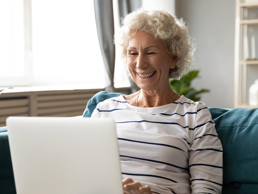 Older woman smiling on sofa at laptop