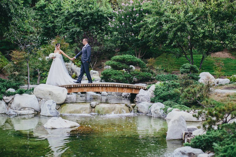 couple holding hands at botanical gardens wedding venue bride walks across a bridge and looks back at groom smiling