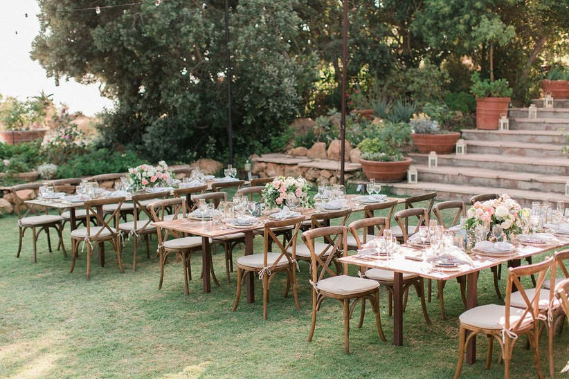 outdoor wedding reception venue with rows of long tables lined with wooden chairs on both sides
