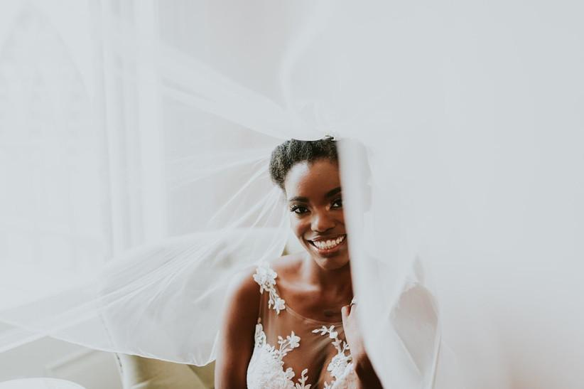 portrait of Black bride wearing veil smiling for the camera