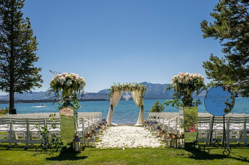 wedding ceremony on green lawn with lake and mountain backdrop