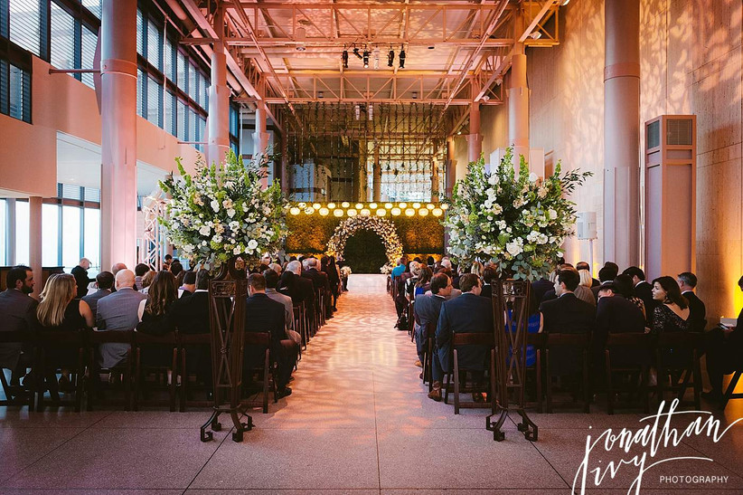 indoor wedding ceremony with floral arch at the altar