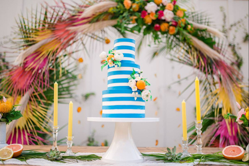 three-tier cake decorated with white and teal fondant stripes, orange ranunculus flowers