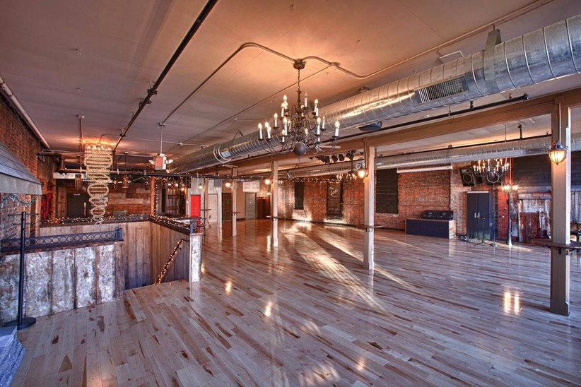 empty loft space with chandeliers and wood floors