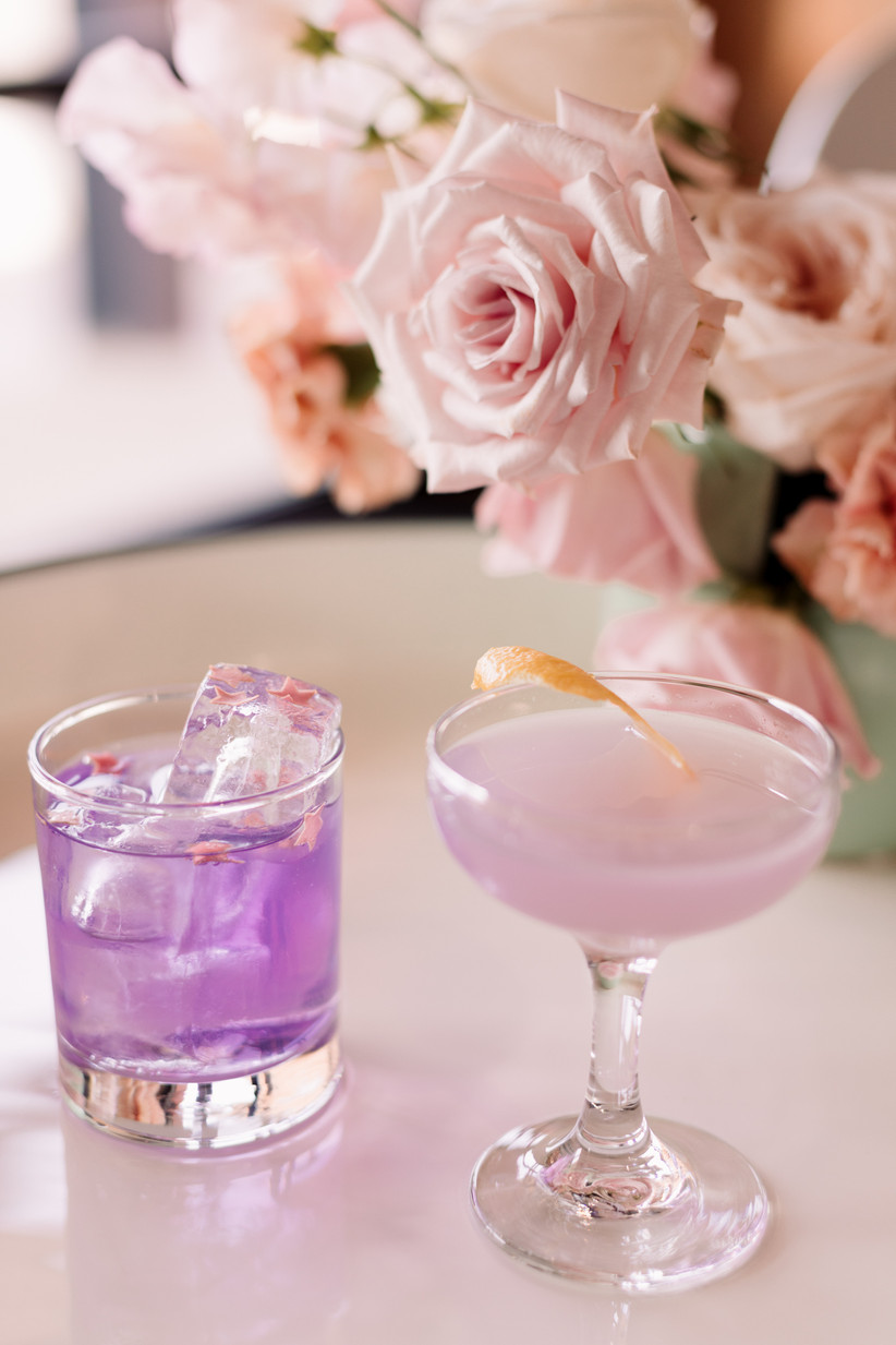close-up of two mixed drinks in purple wedding colors with pink roses in the background