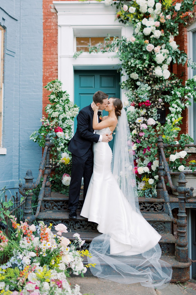 bride and groom stand on the steps of their townhouse with flowers surrounding the door and leading up the steps