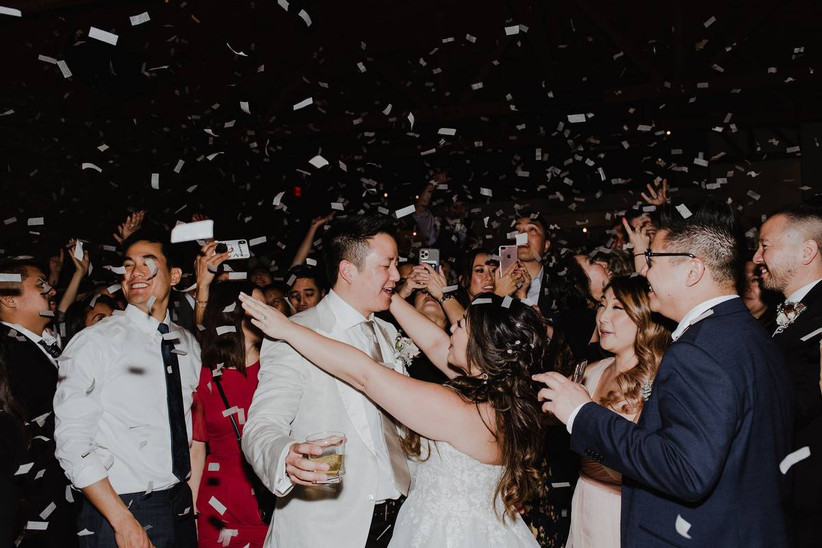 wedding couple and guests dancing as confetti falls around them