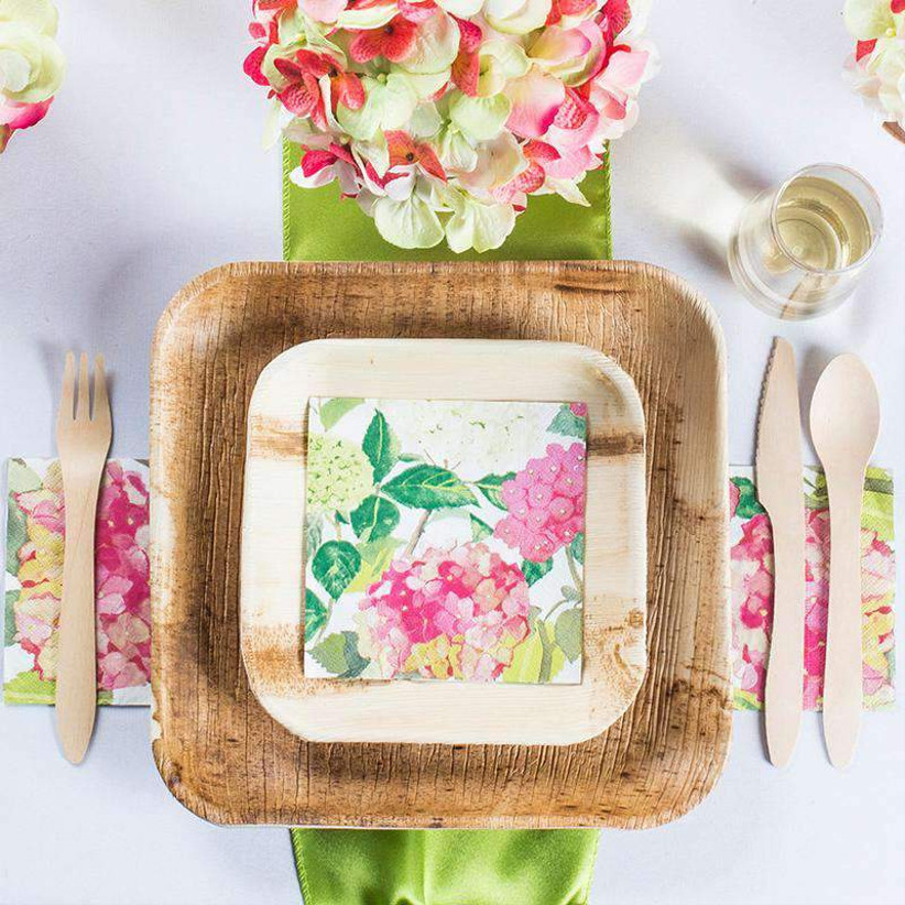 Bright floral place setting with rustic palm leaf plates and cutlery