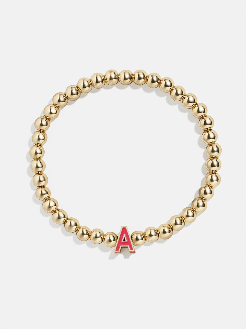 Gold beaded bracelet with bright red letter A charm
