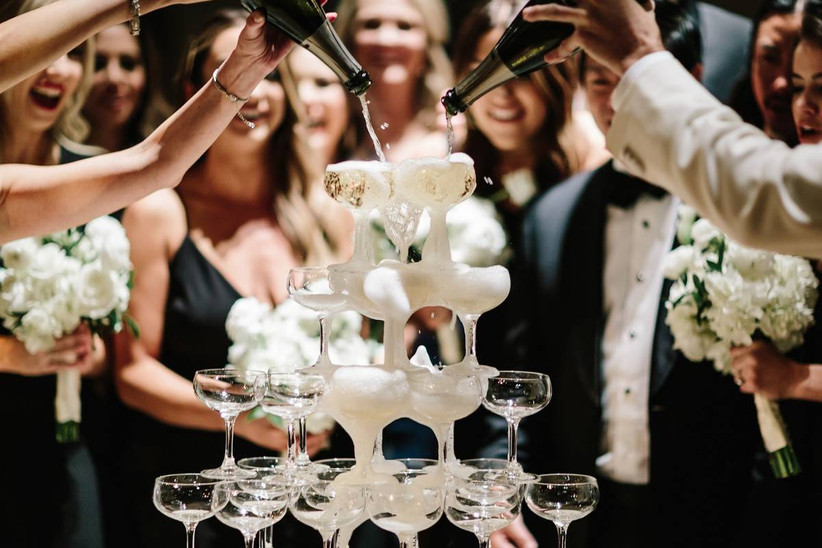 wedding guests pour bottles of champagne down a tower of glass champagne coupes