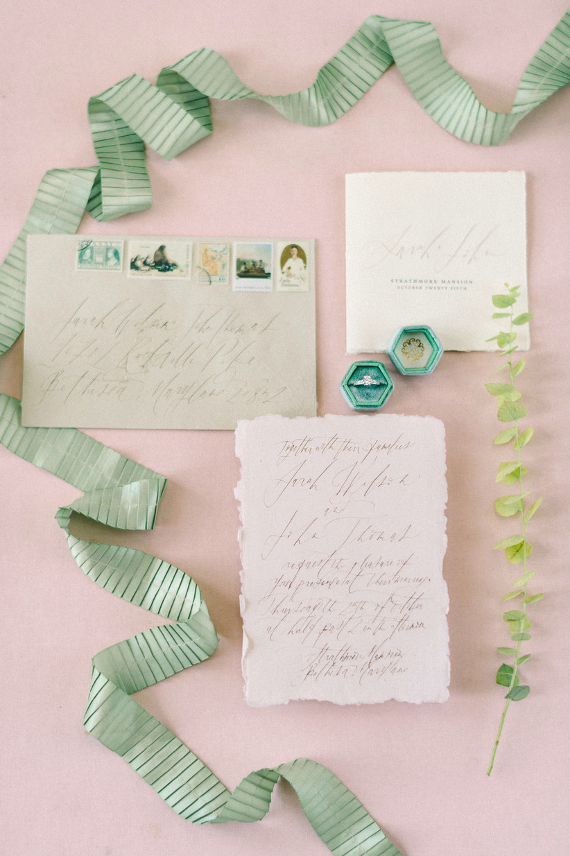 blush and light green wedding flat lay with calligraphy envelope