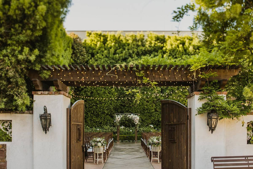 outdoor wedding ceremony botanical gardens wedding venue gates open into courtyard covered with ivy and twinkle lights