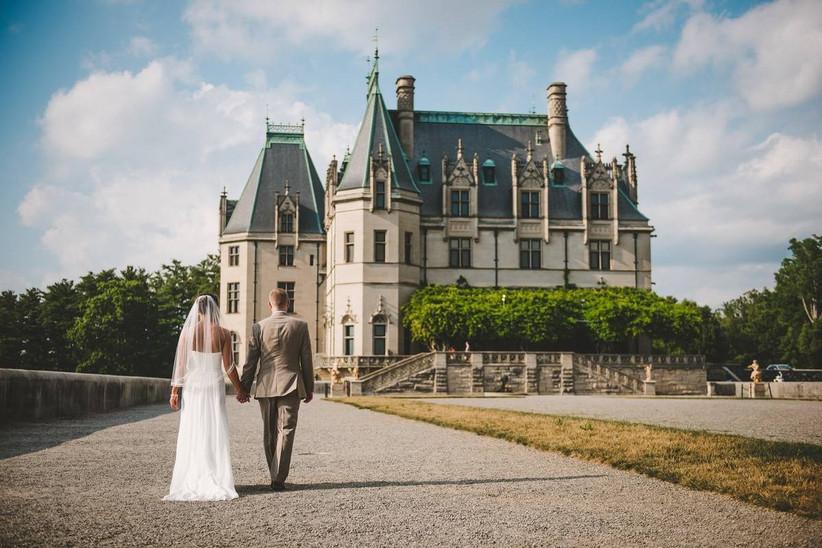 wedding couple walking toward huge biltmore estate