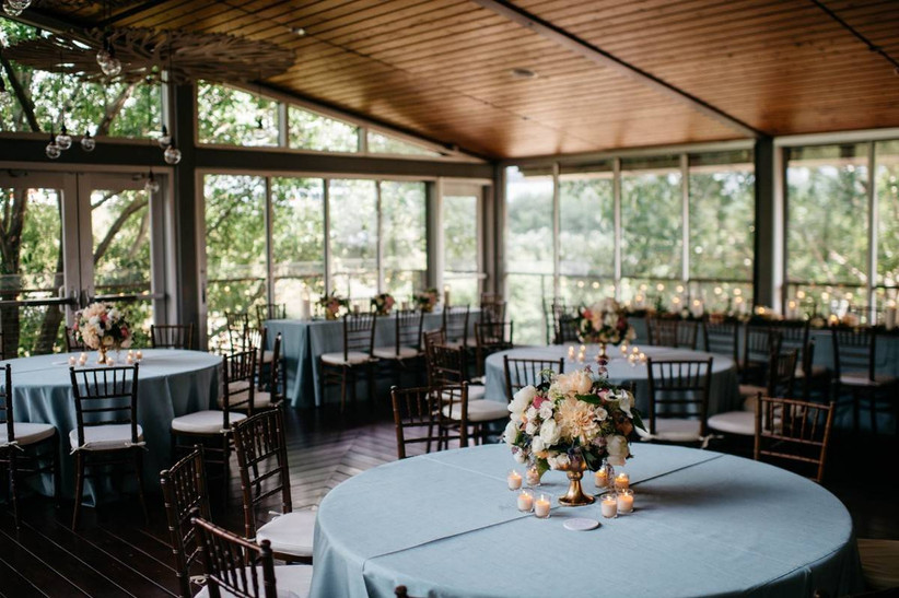 round wedding reception in the foreground with similar tables at the back of the room and windows around the perimeter