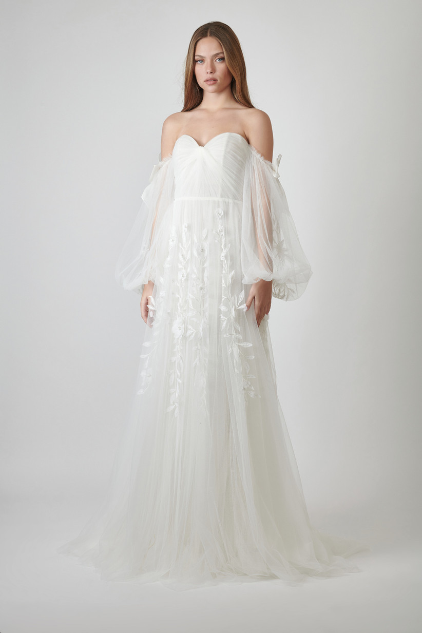 strapless wedding dress with sweetheart neckline and sheer bishop sleeves adorned with floral embroidery