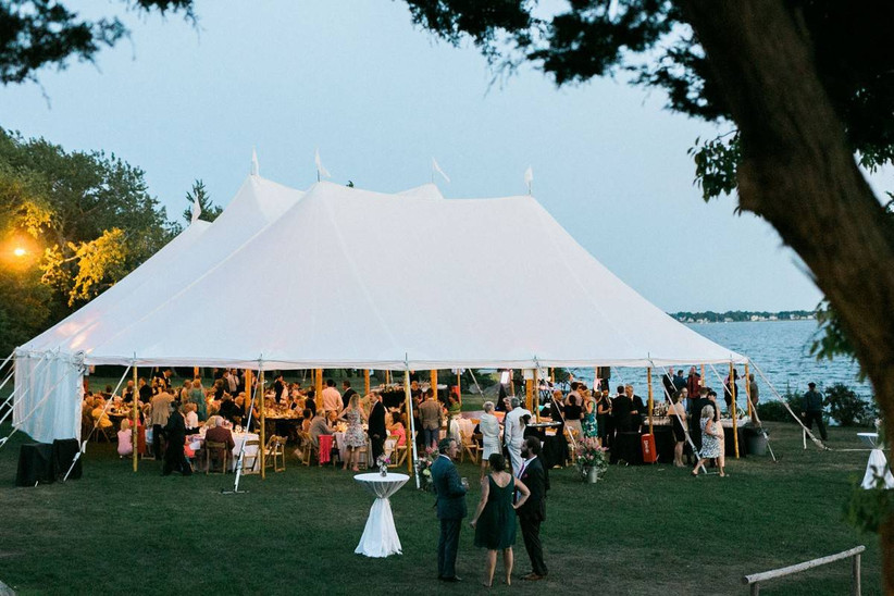 outdoor wedding reception at sunset with sailcloth tent along the water at rhode island wedding venue